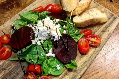 Beet and goat cheese salad served on a wooden cutting board.