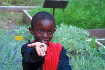 A New Haven elementary student explores Common Ground's children's garden